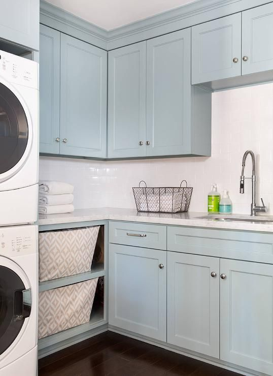 Blue laundry room features blue shaker cabinets paired with white ...
