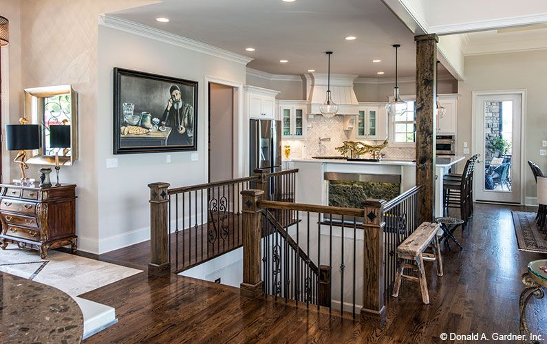 An Art Niche In The Kitchen Island Creates A Focal Point For The | House Plans With Stairs In Kitchen | Upstairs | Country Kitchen | Hidden Pantry | Luxury | Small House
