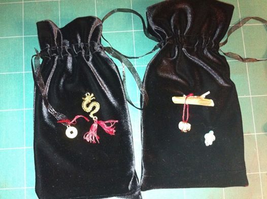 Tarot bags. Photo does not show details very well. A piece of quartz wrapped with copper wire on a piece of cedar and a turquoise turtle bead embellish one bag. A brass finish Chinese coin and dragon embellish the other one.