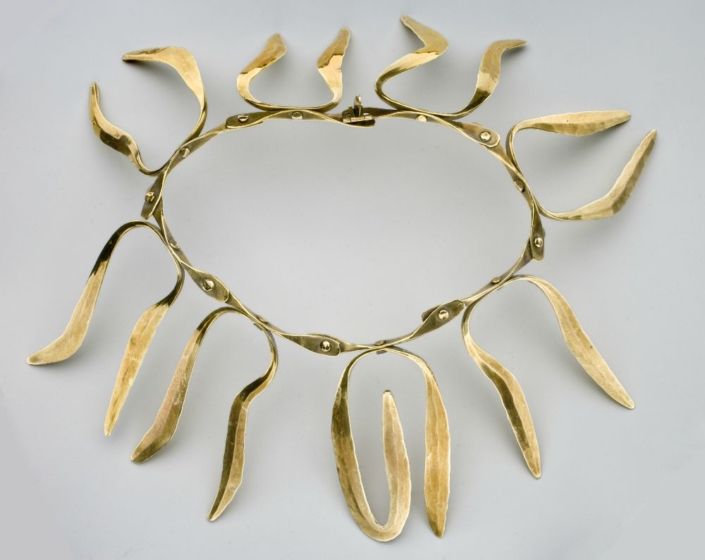 Harry Bertoia, Necklace, Circa 1942–1943. Articulated brass with forged elements and rivets. Choker: 5 ¾ inches circumference. Pendants: 3 ½ x 2 ¼ x 1/8 inches each (approximate). Collection of Cranbrook Art Museum, gift of Dorothy Dunitz in memory of Saul Dunitz. Photograph by R. H. Hensleigh.