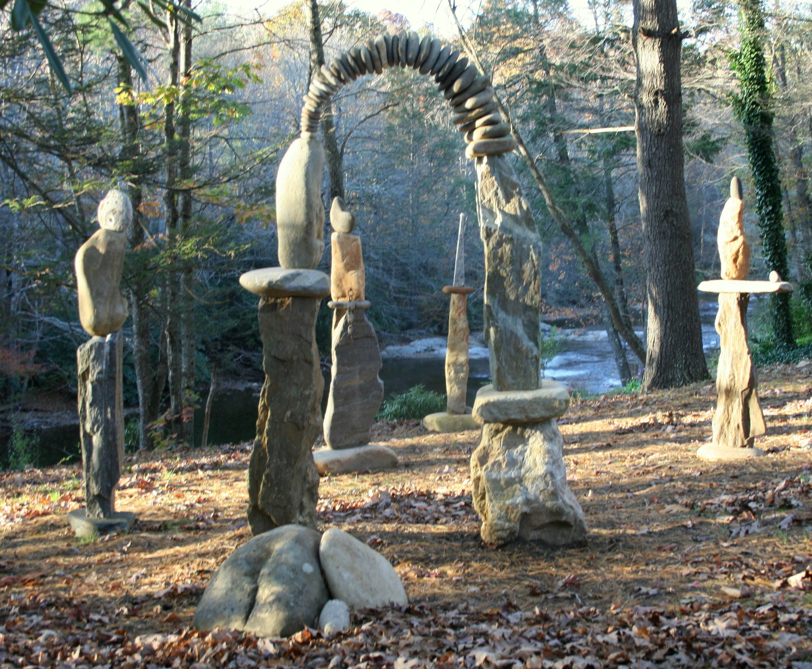 """Stone Sculpture: """"Counsel of Elders"""", came about early on as I was building momentum and knowledge as a stone sculptor. It is a themed comission to represent balancing essentials of healthy human being. Looking through the arch are """"Freedom"""" and """"Guidance"""", to the far right """"The Gift"""", on the left """"Thought"""" and the arch symbolizes partnership and community.  This image is of the group as I arranged them to resemble their relationship when installed."""