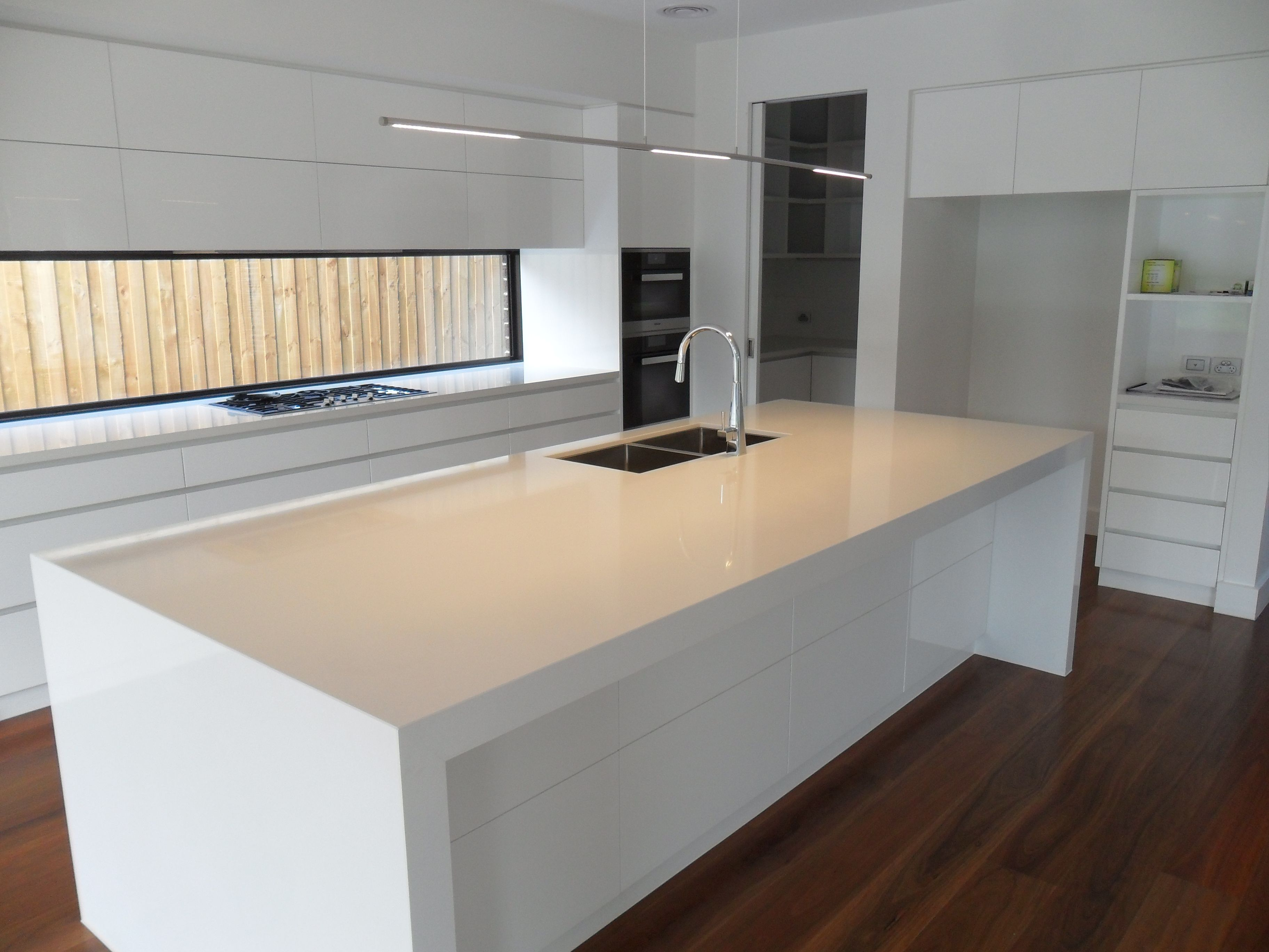 Contemporary kitchen in white. Fixed window as a splash-back, sink ...