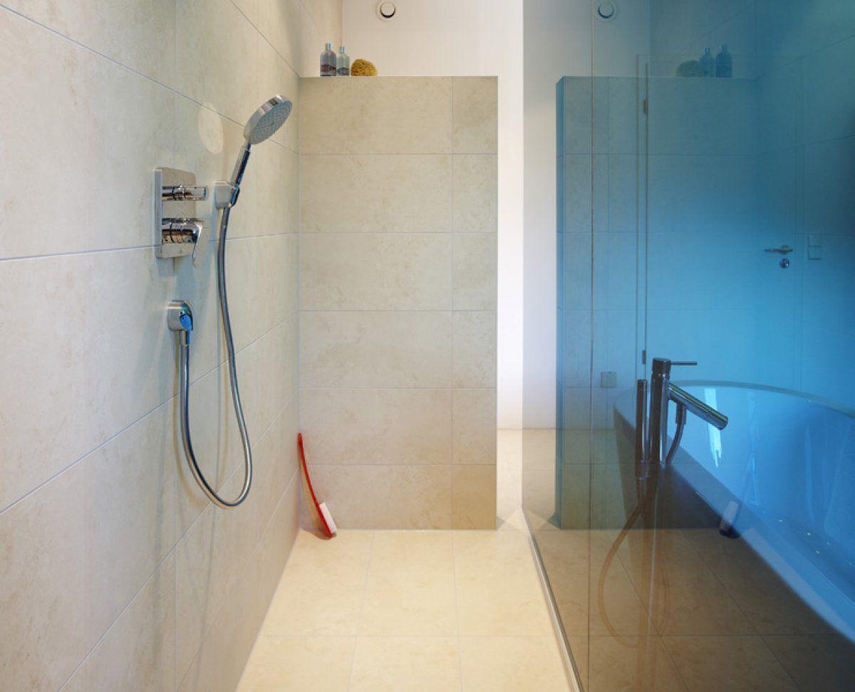 Die große, ebenerdige Dusche wird durch eine raumhohe, petrolfarbene Glaswand vom Raum abgetrennt.