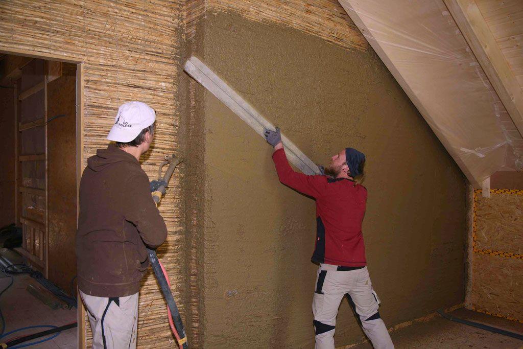 Lehmputzer beim Verputzen einer Holzwand mit Schilfrohrmatte als Putzträger