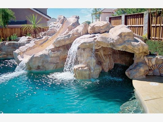 Rock Waterfall With Water Slide Pool Waterfall Pool Water Features Affordable Swimming Pools
