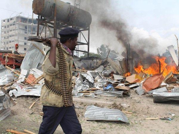 2013 - Mogadishu, Somalia, 12 de julio de 2013 - Un soldado somalí camina junto a casas en llamas, cerca del edificio de las Naciones Unidas, después de que un terrorista suicida detonara explosivos cerca de un convoy de tropas de la Unión Africana en Mogadishu. El grupo insurgente al-Shabaab, que tiene lazos con al-Qaeda, se adjudicó los ataques en Somalia, además de los asesinatos en el Centro Comercial Westgate en Kenia de este año.