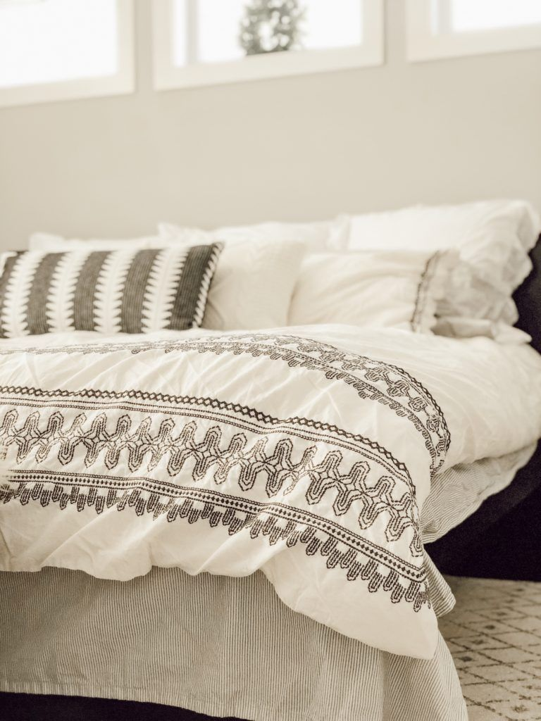 Modern farmhouse style bedding in this cozy master bedroom