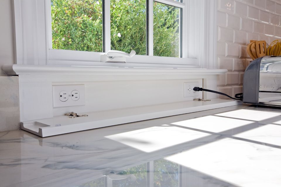 Electrical outlets at backsplash are concealed with window molding ...