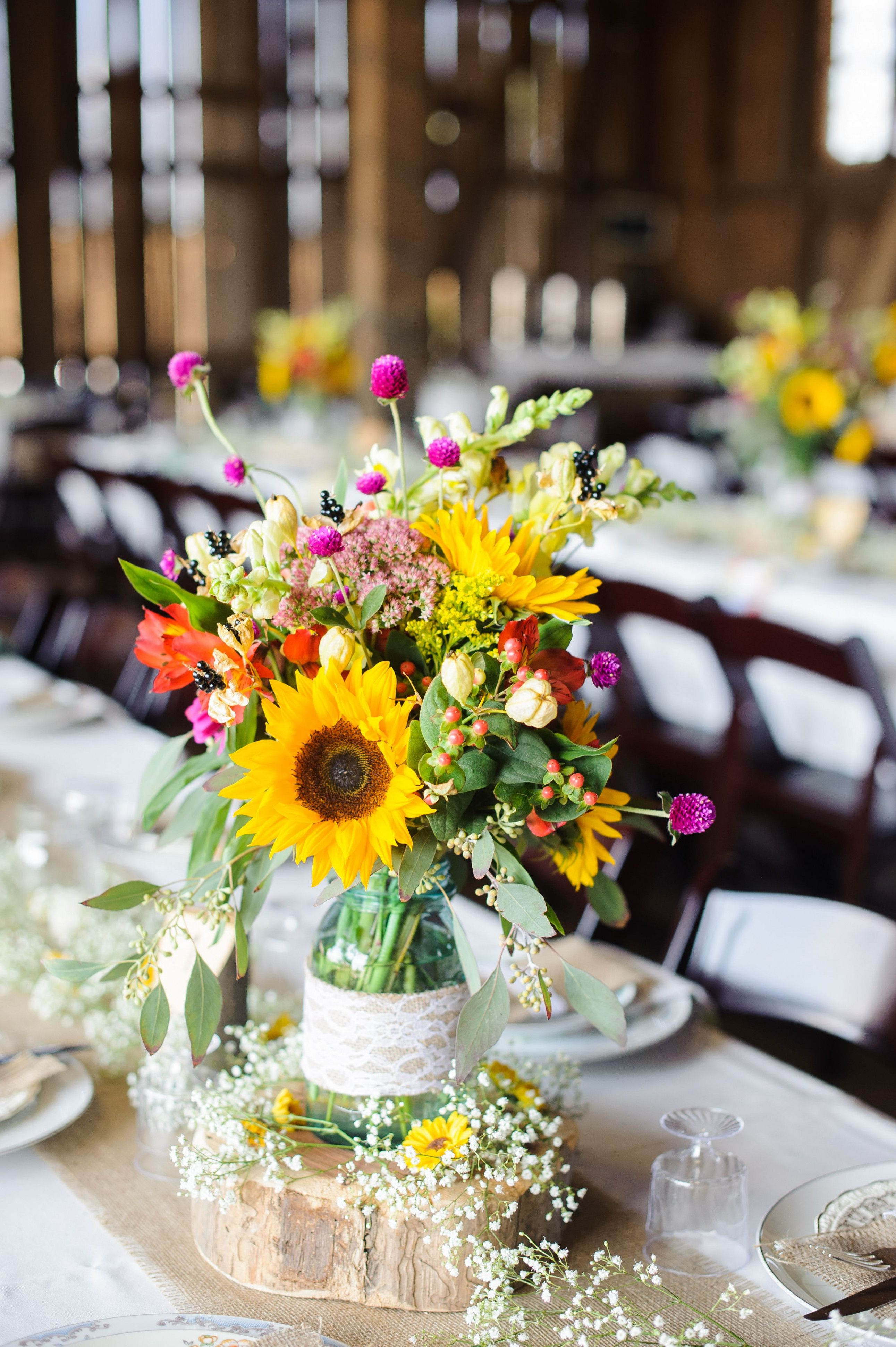 Pink and yellow centerpieces in mason jars on burlap table runners