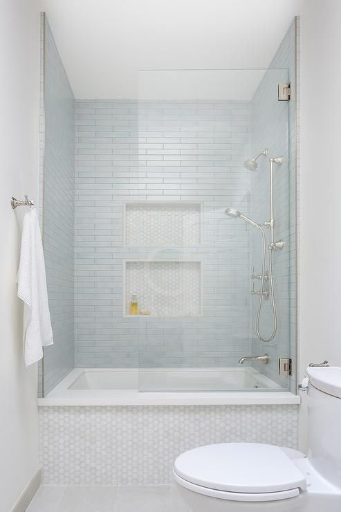 Photo of Thin blue staggered bath shower tiles in a white marble hex tiled bathtub enclos…