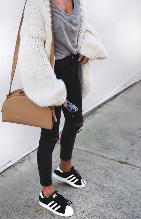 Look com blusa cinza com blusa de tricô e calça preta e tênis