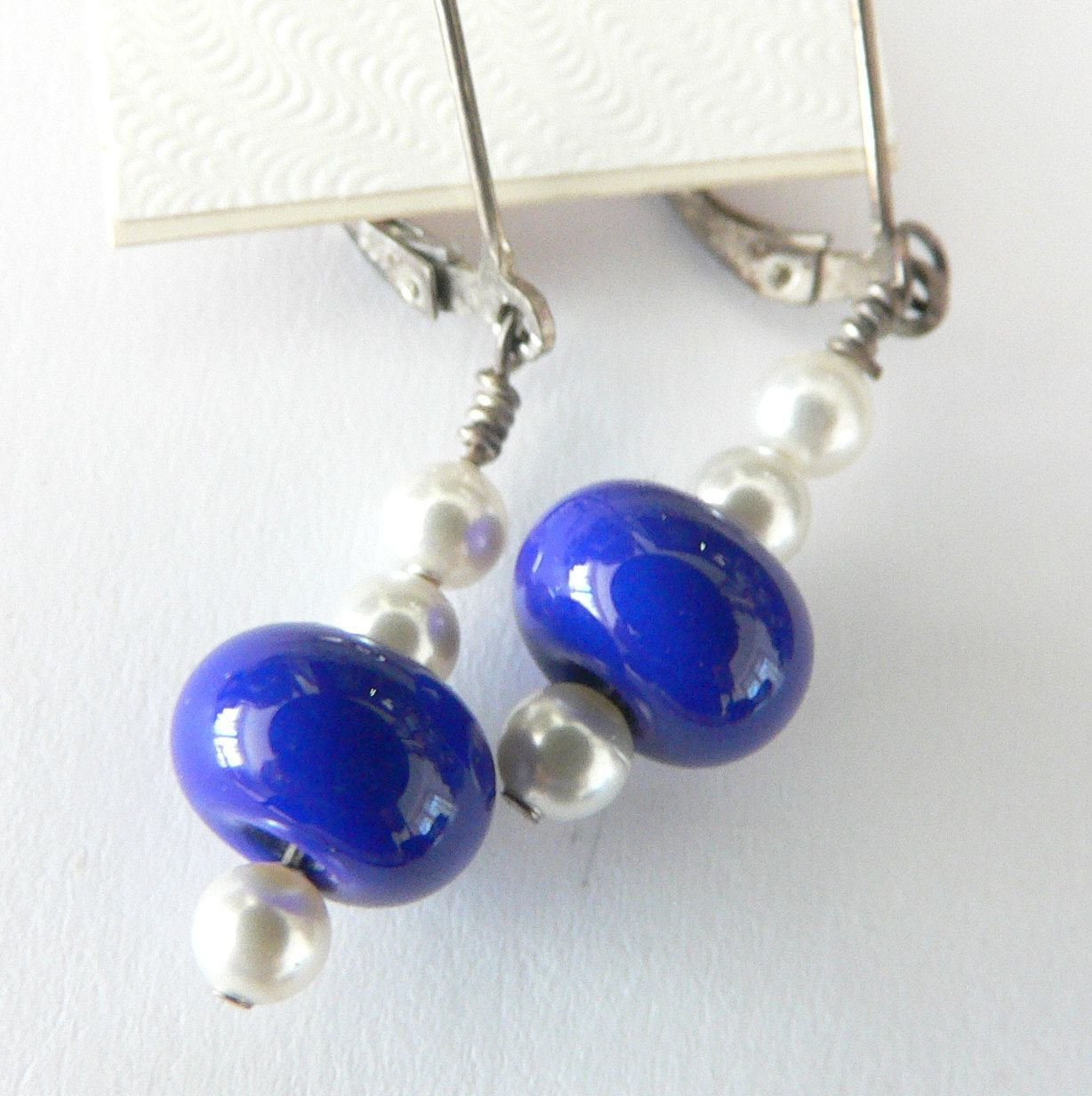 Maineteam My lampwork beads of lapis blue and small pearls sterling silver dangle earrings. $15.00, via Etsy.