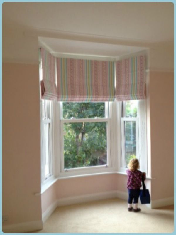 Admiring her new Roman blinds fitted to a beautiful Edwardian bay window.