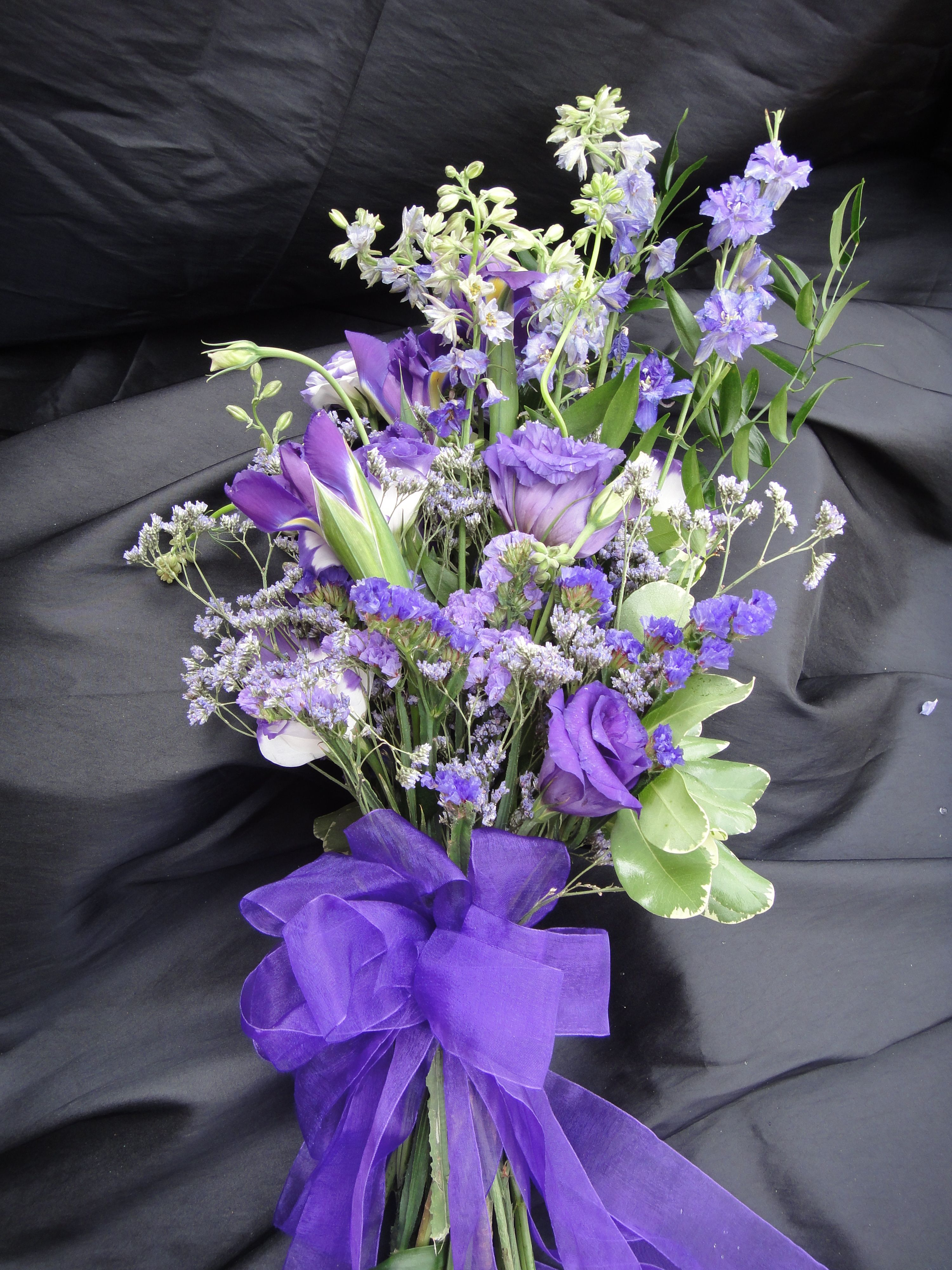 Purple Bouquet Designed Using Larkspur Lisianthus Iris Caspia Statice Wedding Bouquets Purple Bouquet Country Wedding