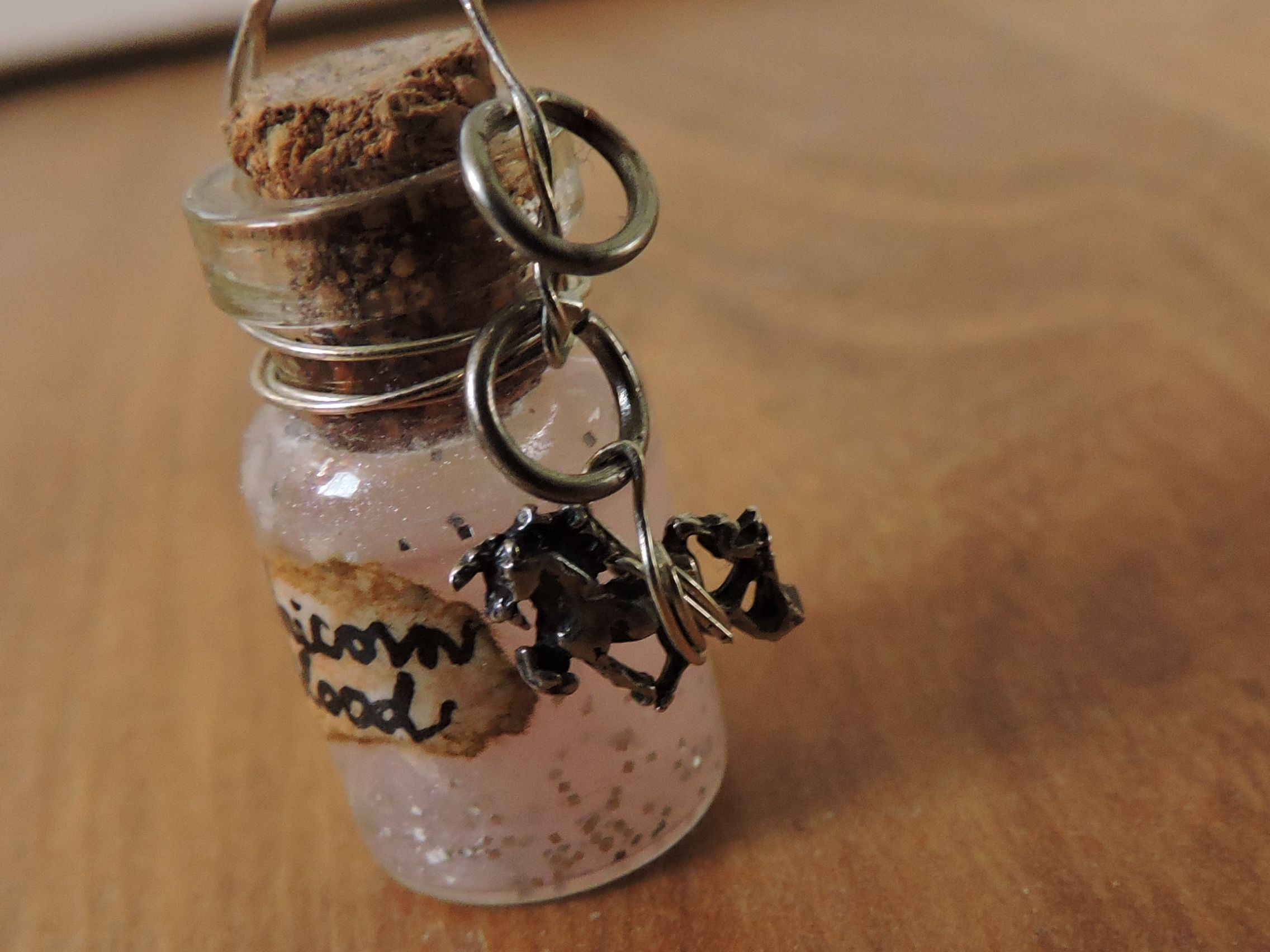 Unicorn Blood--Bottle charm pendant using small glass bottle with glitter and colored glue inside of it, and a silver unicorn charm attached to it.
