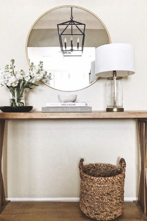 A simple entryway table makes a grand statement with a lantern pendant, decorative mirror…