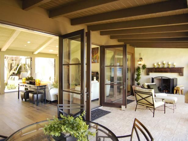 Glass doors provide an open, airy environment that allows the indoors to easily unite with the outdoors.  From HGTVRemodels.com Have outdoor built in BBQ in place of fireplace.