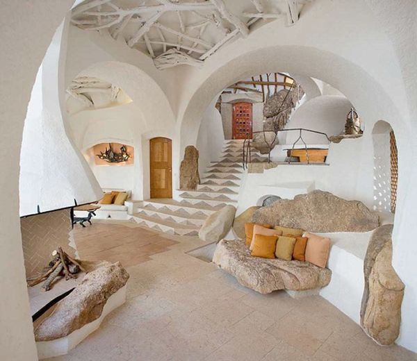 I love the curvilinear walls/ceilings and the boulders, though I'm not so fond of the white paint on those lovely branching rafters.  From - Handmade Houses: A Century of Earth-Friendly House Design