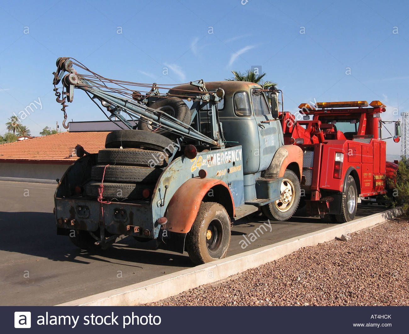New tow truck towing old tow truck stock photo