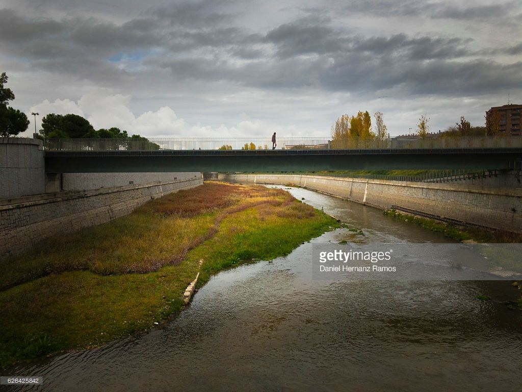 Stock Photo : One lonely man walking in a bridge over a river. Madrid. Spain