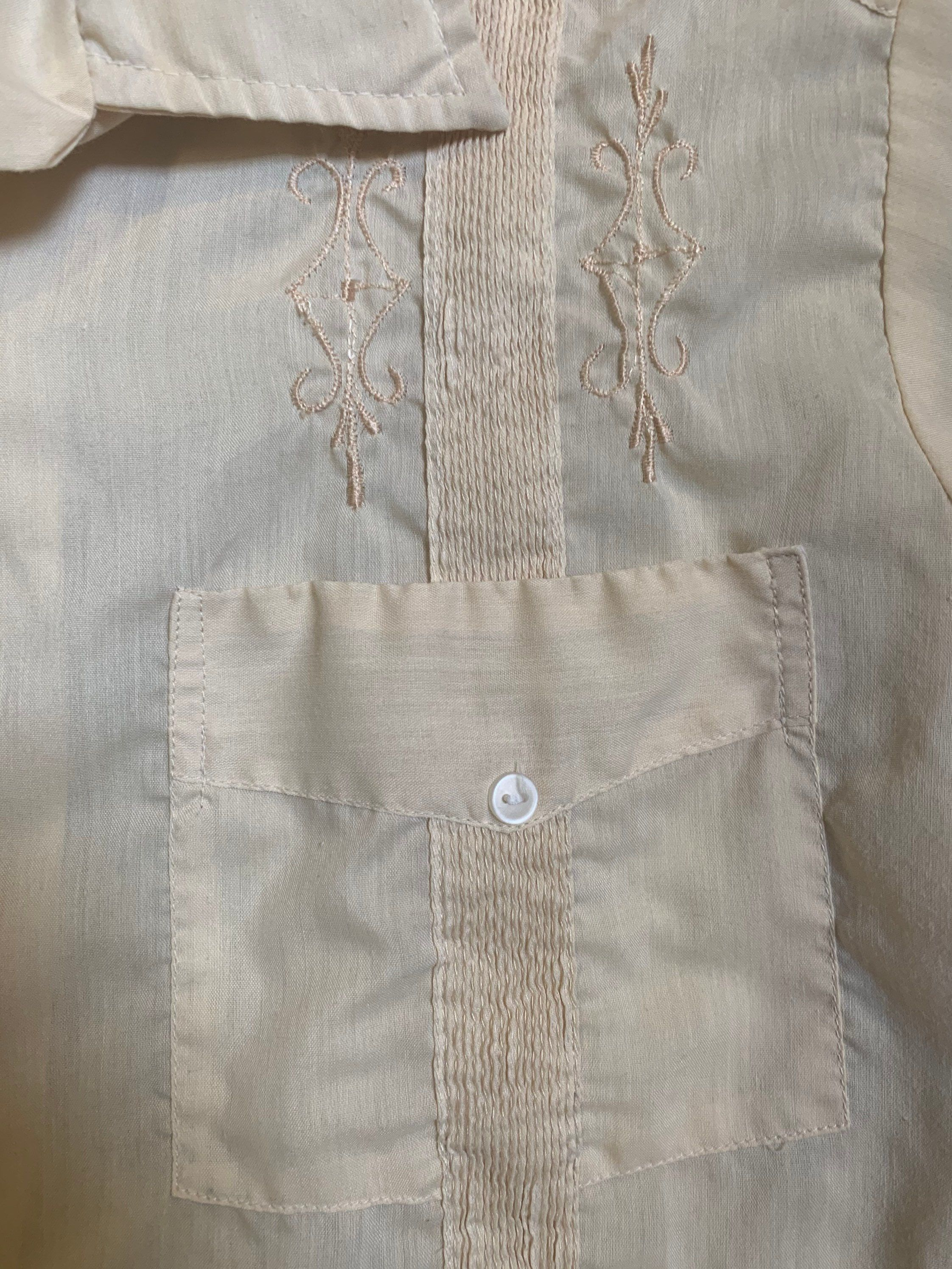 Lovely Guayabera shirt of the 1970s! Polyester and cotton blend. Nice detailing and rich cream color! Size extra large. Chest: 24.5 inches across Waist: 24 inches across Entire length of garment: 28 inches Shoulder to shoulder on back: 20 inches across