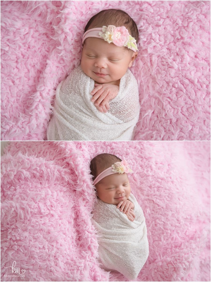 Sleeping newborn girl pink and smiling