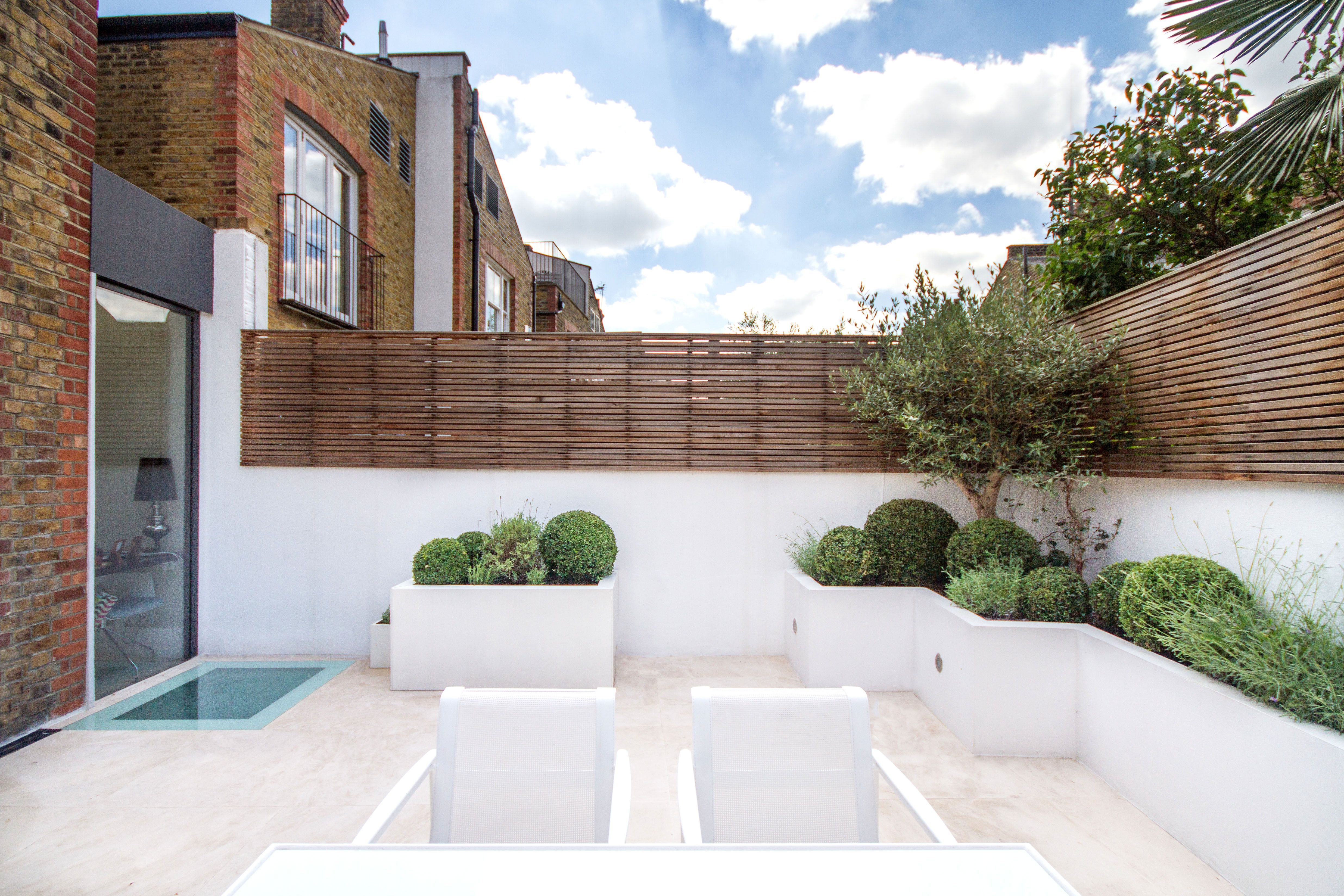 White Rendered Raised Beds And Limestone Paving With Slatted Trellis