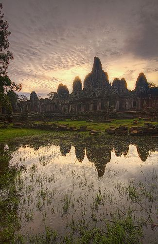Sunrise at Bayon Temple  Morning light is reflected in rainwater at Bayon Temple in Angkor Thom near Siem Riep, Cambodia. Bayon is well known for it's giant Buddha faces at adorn its walls. It was built sometime in the late 1100's ASunrise at Bayon Temple