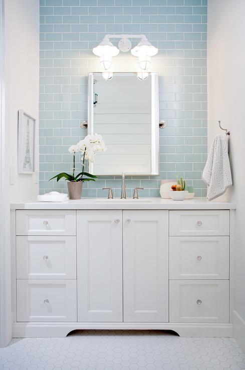 Charming white and blue bathroom boasting white hex floor tiles