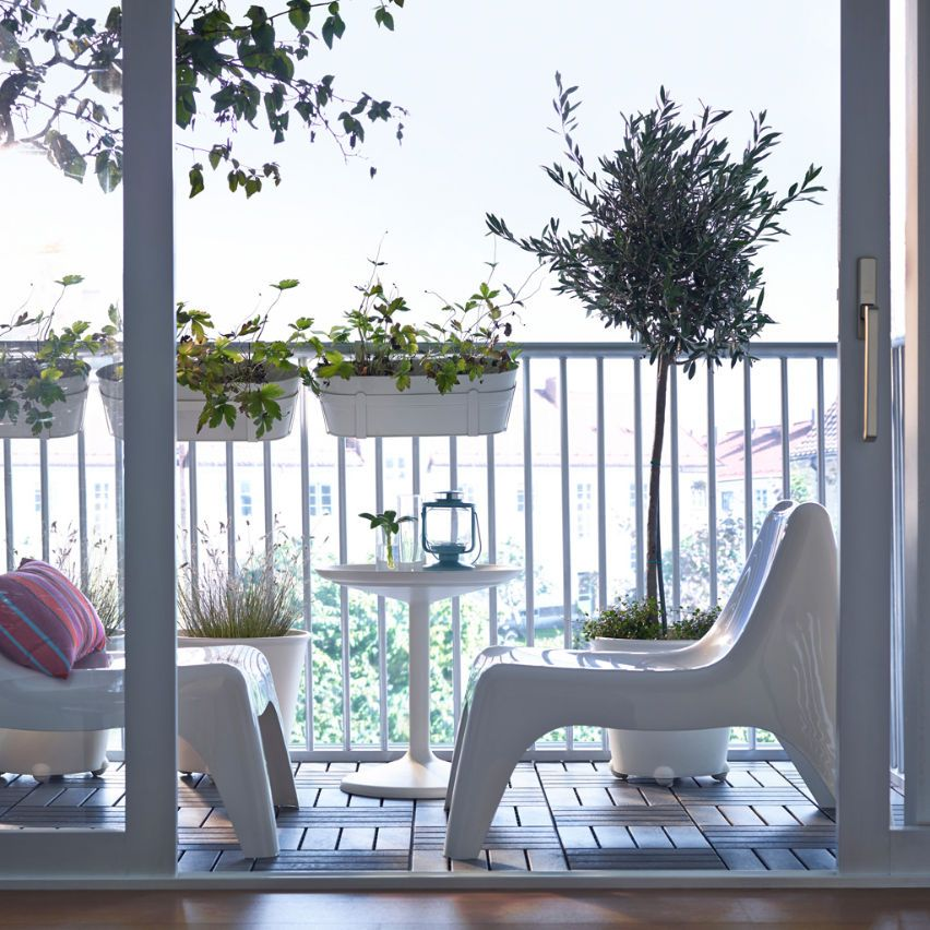 A Balcony With Low Plastic Chairs, Round Tray Table And Hanging Flower  Boxes, All