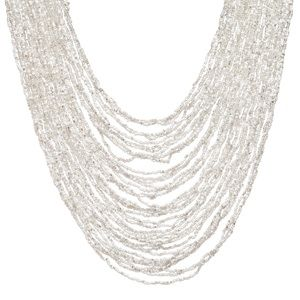 """Drape yourself in luxury when you slip into this multi-strand bib necklace comprised of clear and white seed beads. The handmade macramé and bead closure adds just the right panache! - Seed beads, macramé - 26"""" long - Bead & loop macramé closure  Item # MIT30001010"""