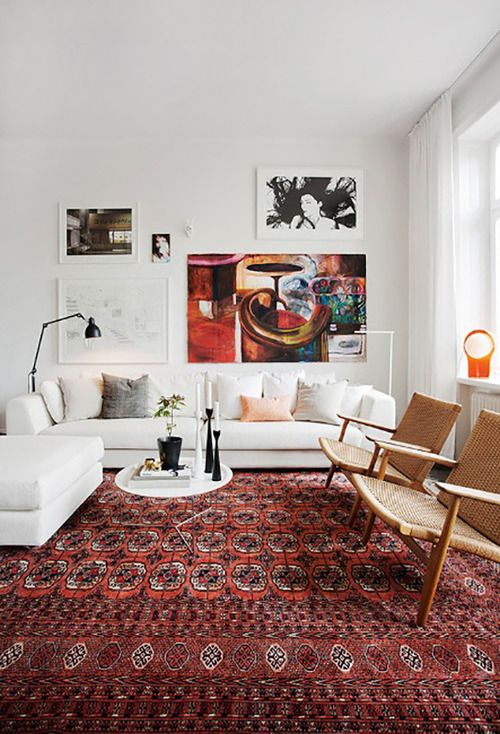 Warm cozy living room with oriental rug white sofa danish modern chairs gallery art wall also what do you think about artwork being stacked or rested on