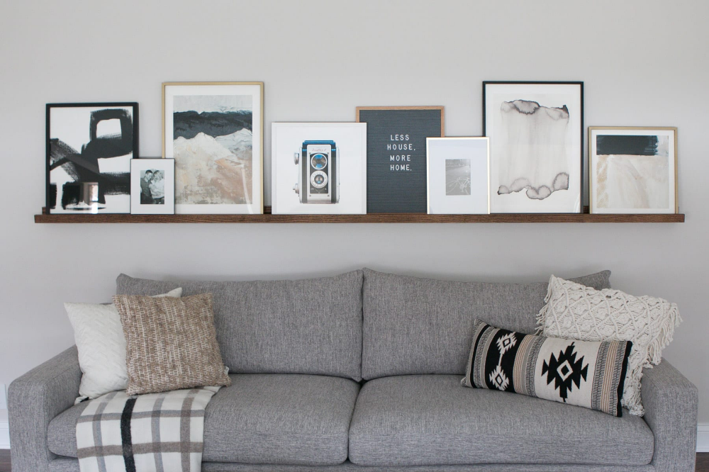 DIY Picture Ledge Over the Couch Filled with Art is part of Wall decor living room, Living wall decor, Kid room decor, Room wall decor, Living room decor, Living room wall - A DIY Picture Ledge is a perfect option to display assorted art  Get the details on how you can make a DIY Picture Ledge for your space!