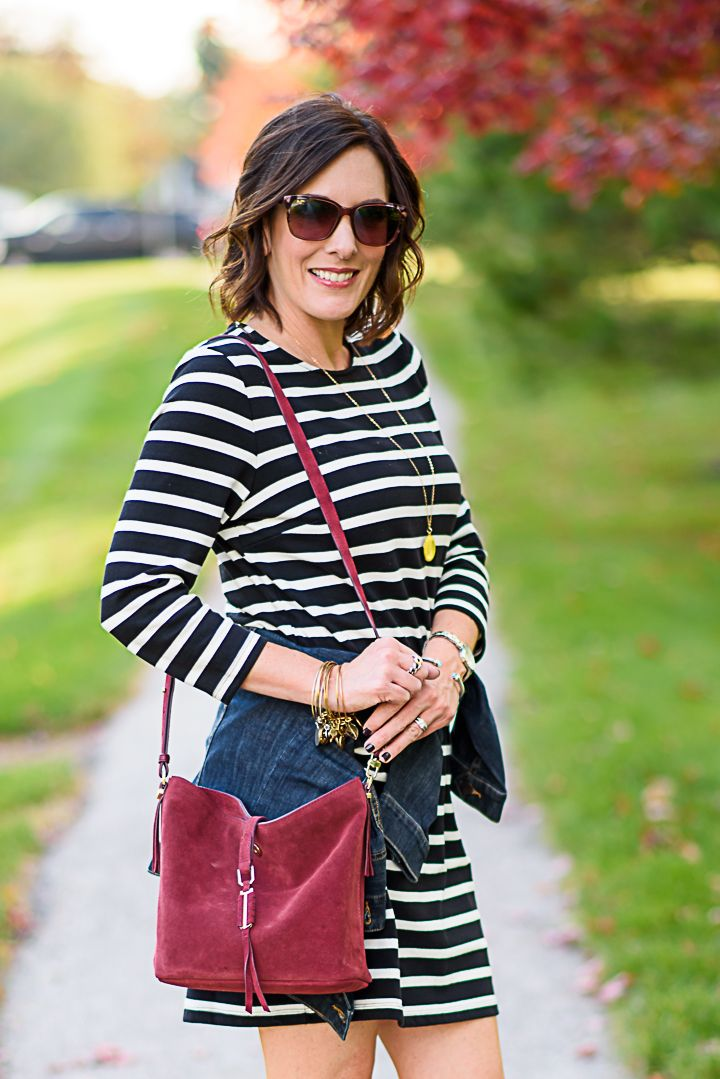 aa7f552c8c3 How to Wear a Black and White Striped Dress Outfit for Fall  with a denim  jacket and burgundy bucket bag