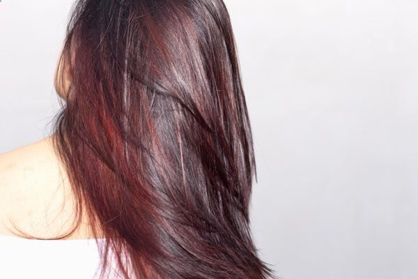 chocolate brown hair with cherry red low lights | For a fun way to color hair, add some bold streaks to your bangs! You ...