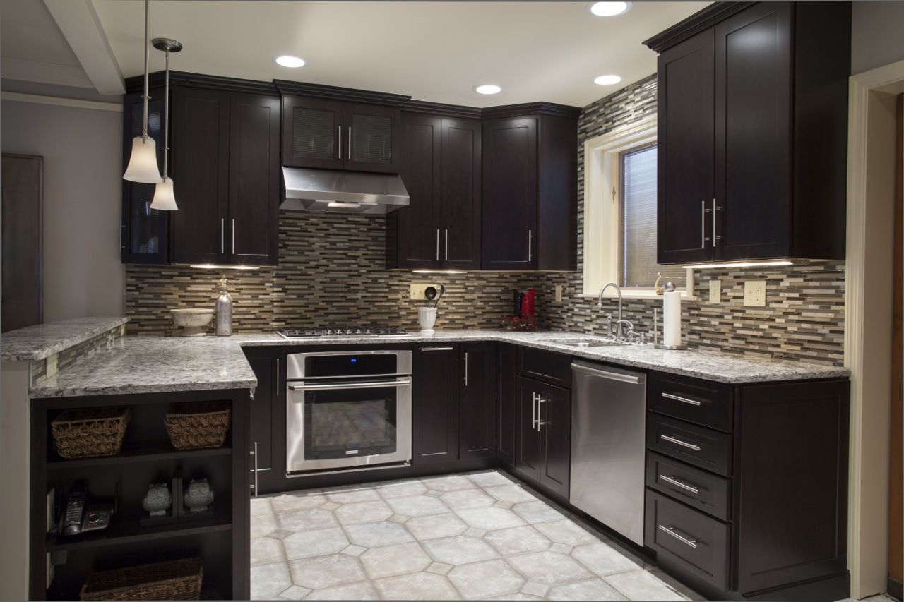 A medium kitchen with dark cabinets and light floor make for a ...
