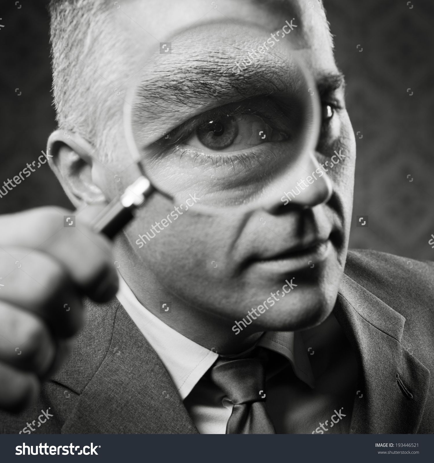 Vintage Detective Looking At Camera Through Magnifying Glass