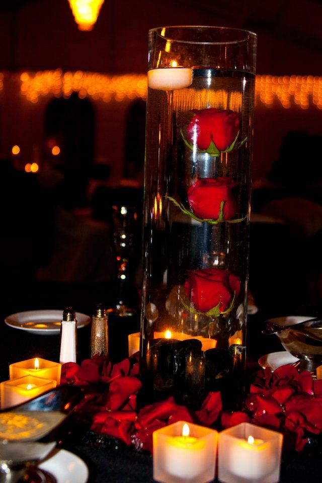 Simple centerpiece with three roses suspended in water