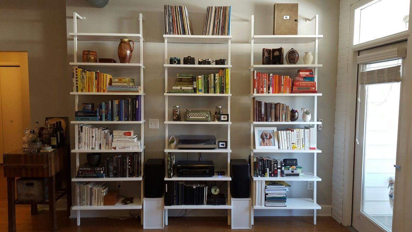 White bookshelves with color-coded book organization