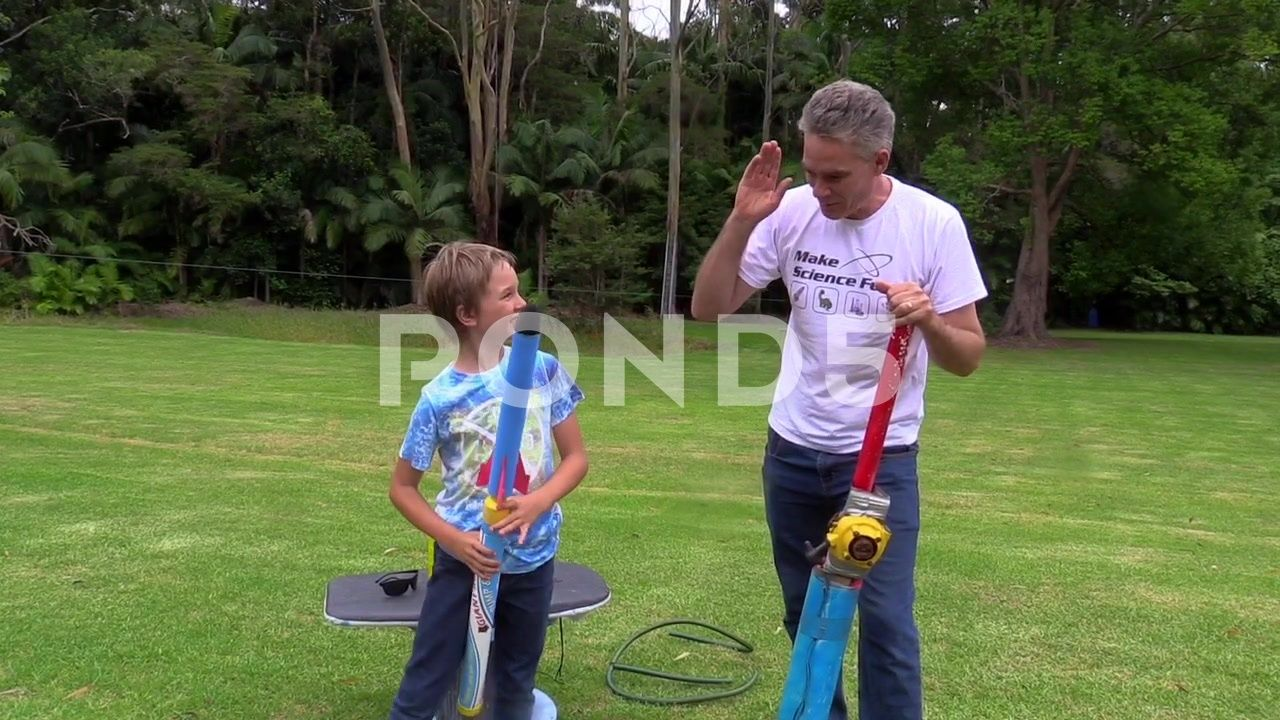 Nutty professor dad and son adapt toy rocket launcher for extra fire power Stock Footage sonadapttoyNutty