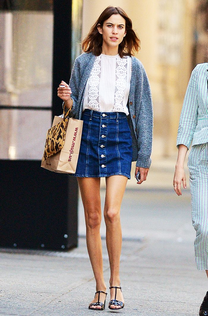 010a3e84c7 Alexa Chung wears a denim A-line mini skirt with a white blouse, gray  sweater, and black sandals