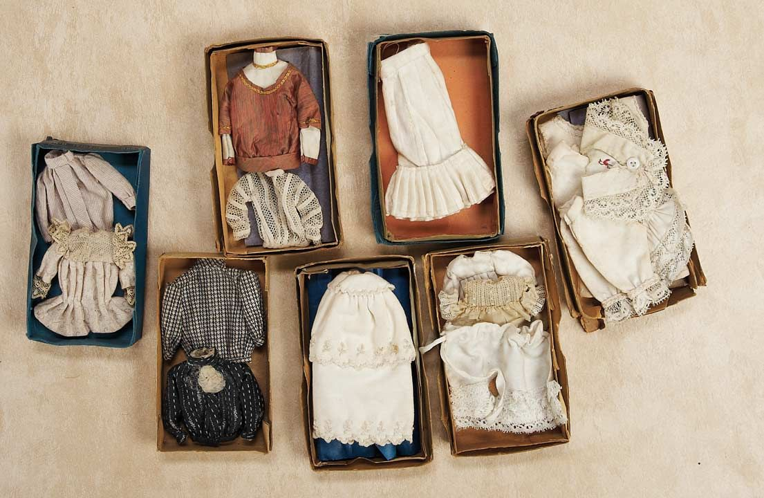 """Theriault's - Miniature Costumes in Original Boxes from Old Store Stock. 5.5""""x2.5"""" boxes with costumes for mignonettes, blouses, little dresses, undergarments, a beautiful pique cape with capelet collar and embroidery. c 1890"""
