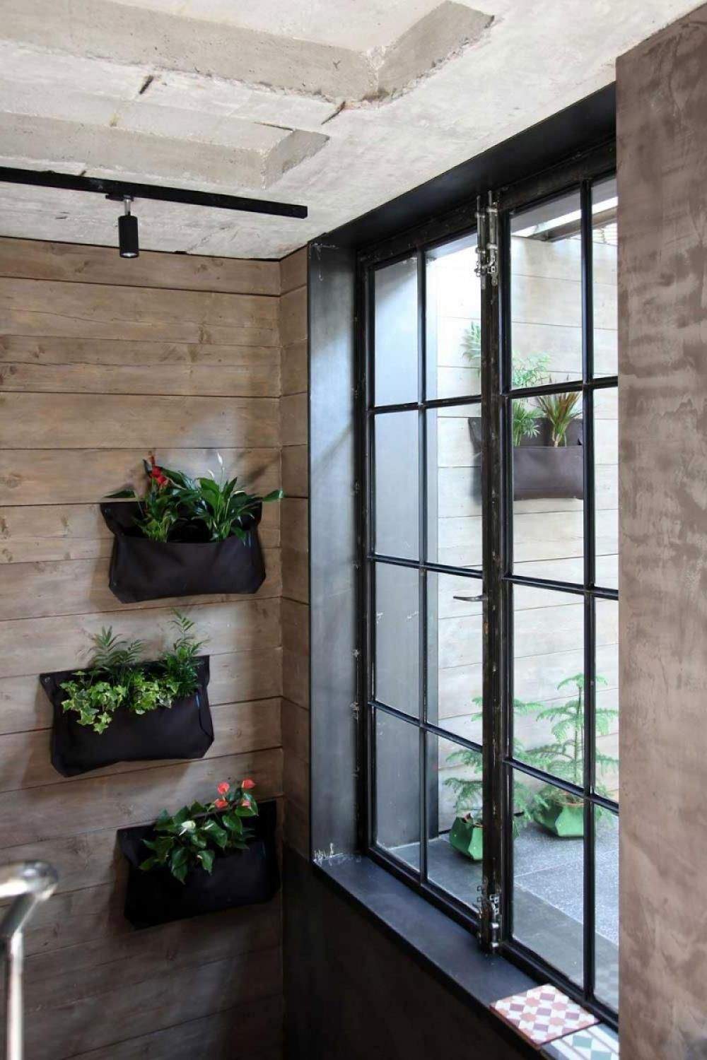 green wall design in wooden wall with exposed concrete ceiling