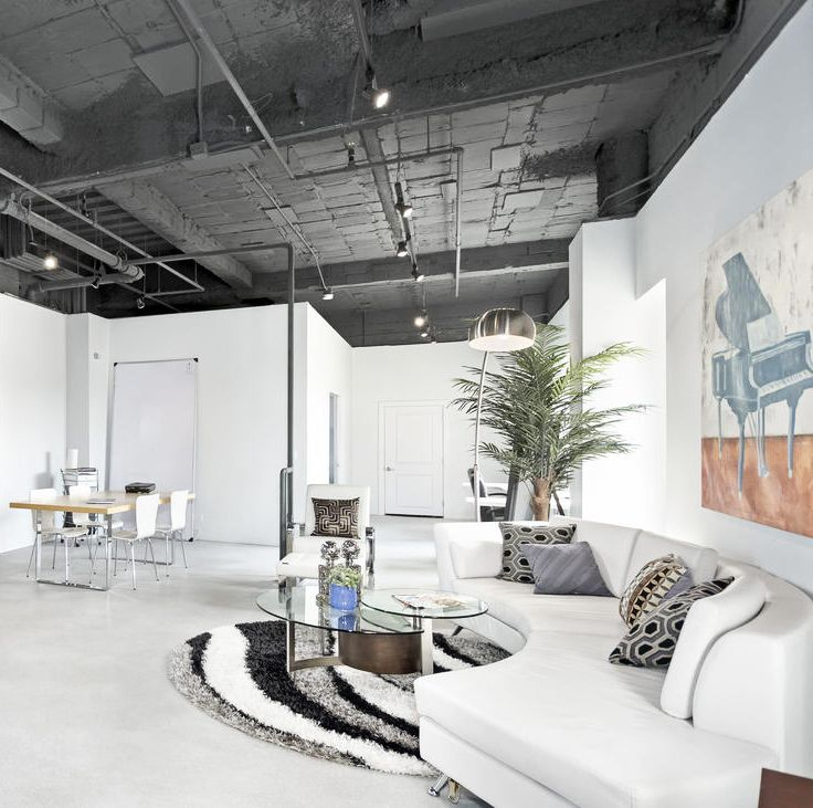A grey color palette sleek surfaces and exposed ceiling give this downtown two story