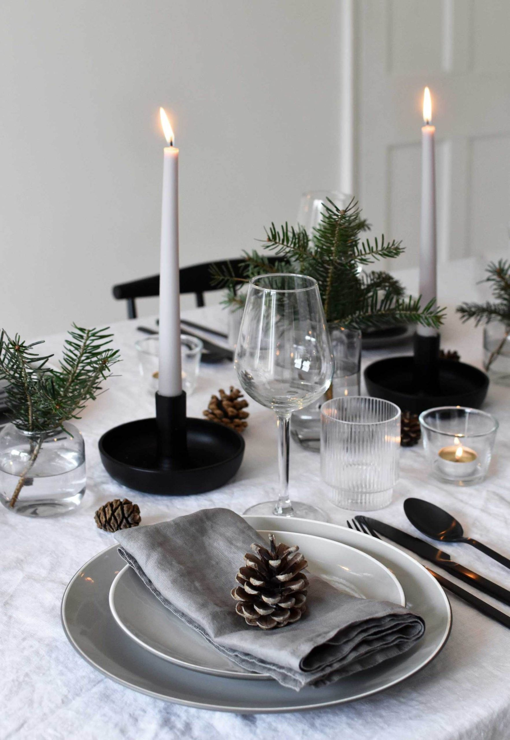Minimalist Christmas table styling with fir candles  pine cones Minimalist Christmas table styling with fir candles  pine cones