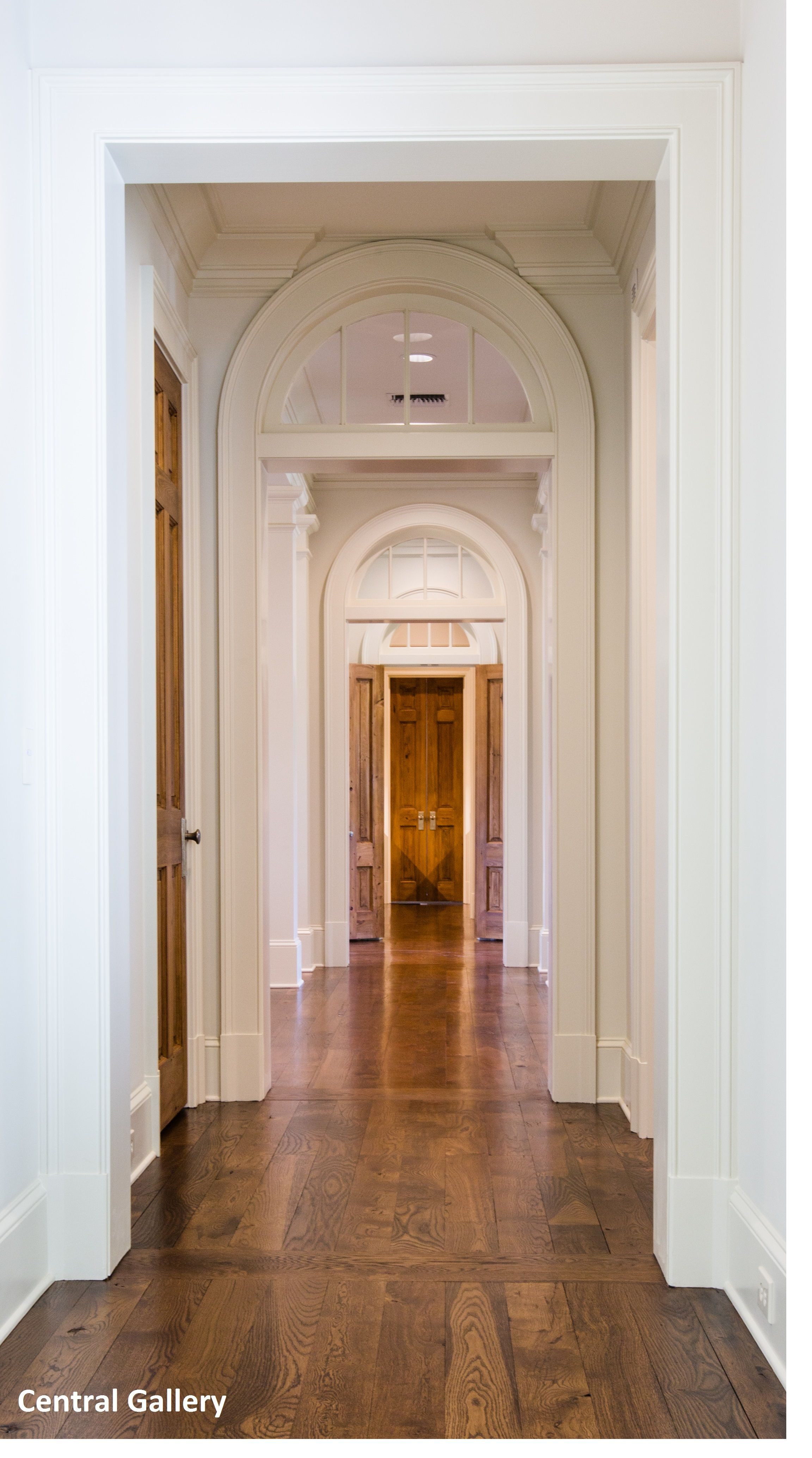 Gallery hall of arched top doors and transoms, antique oak floor, antique cypress doors.