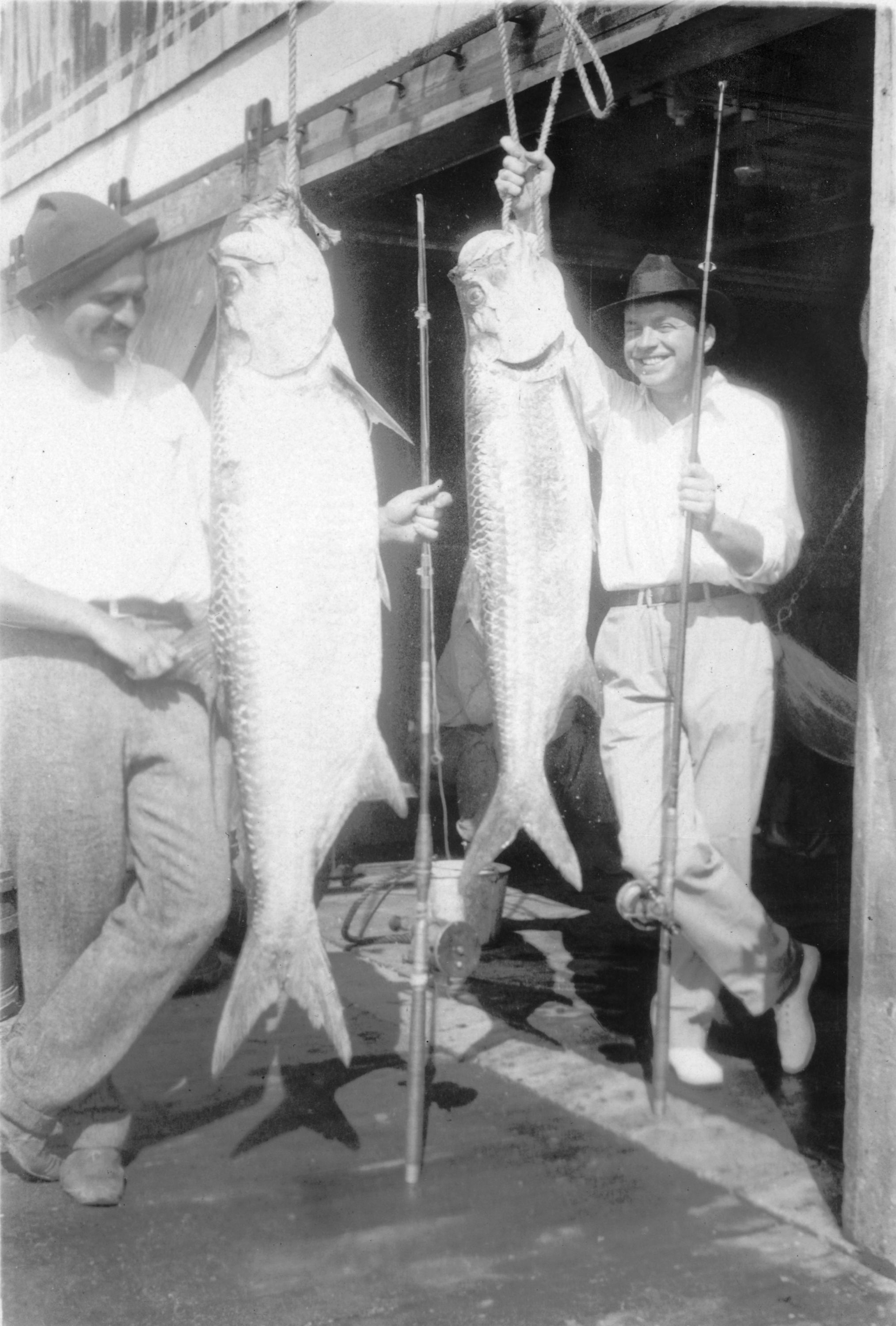 Ernest Hemingway and John Dos Passos pose with two tarpon fish, Key West, 1928.