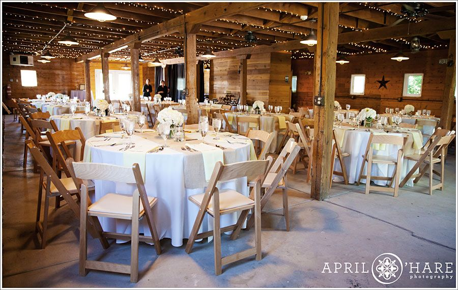Tables set up inside the barn at a summer wedding reception at