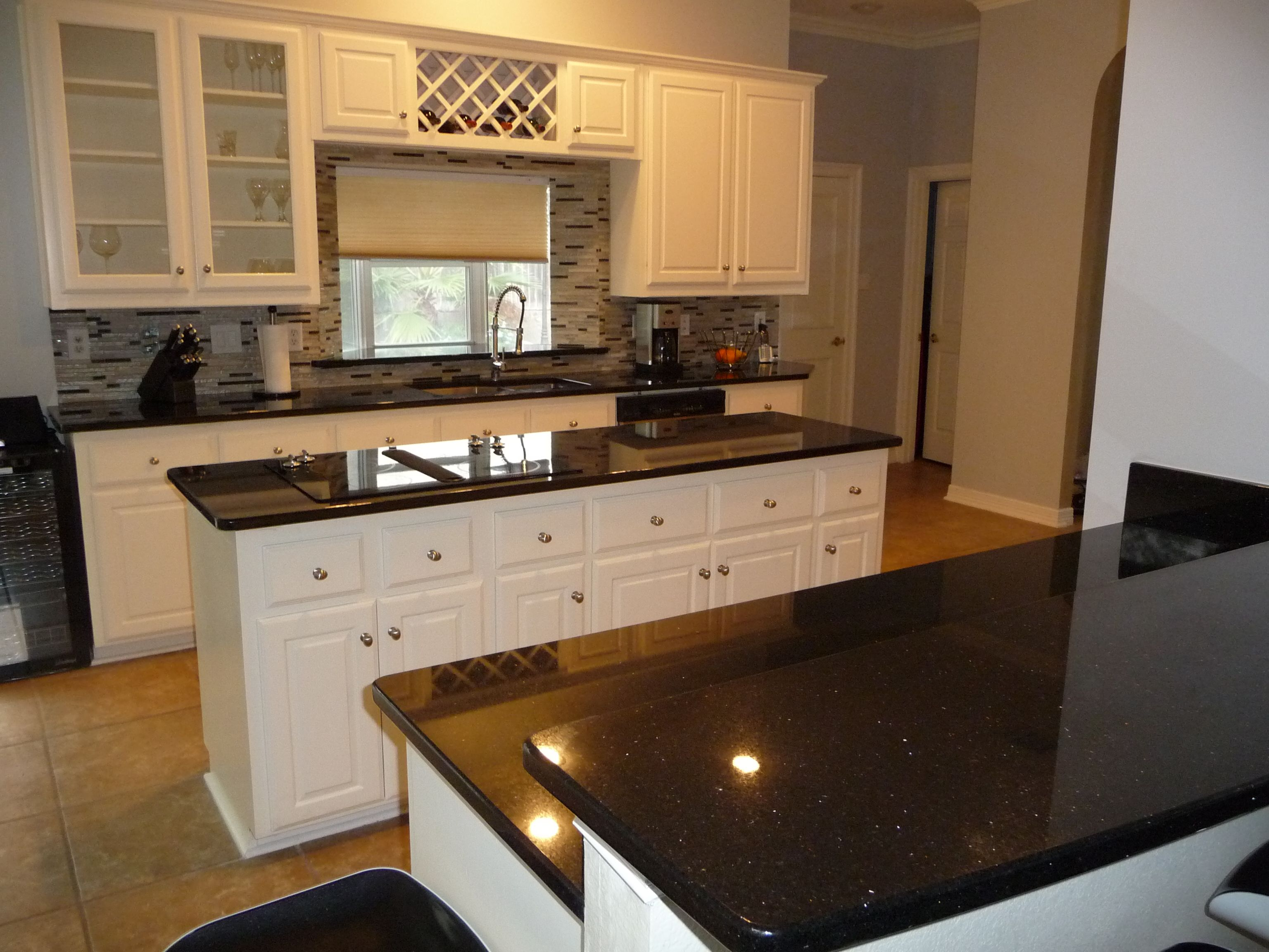Love black and white kitchens black galaxy granite for Black kitchen cabinets with white marble countertops