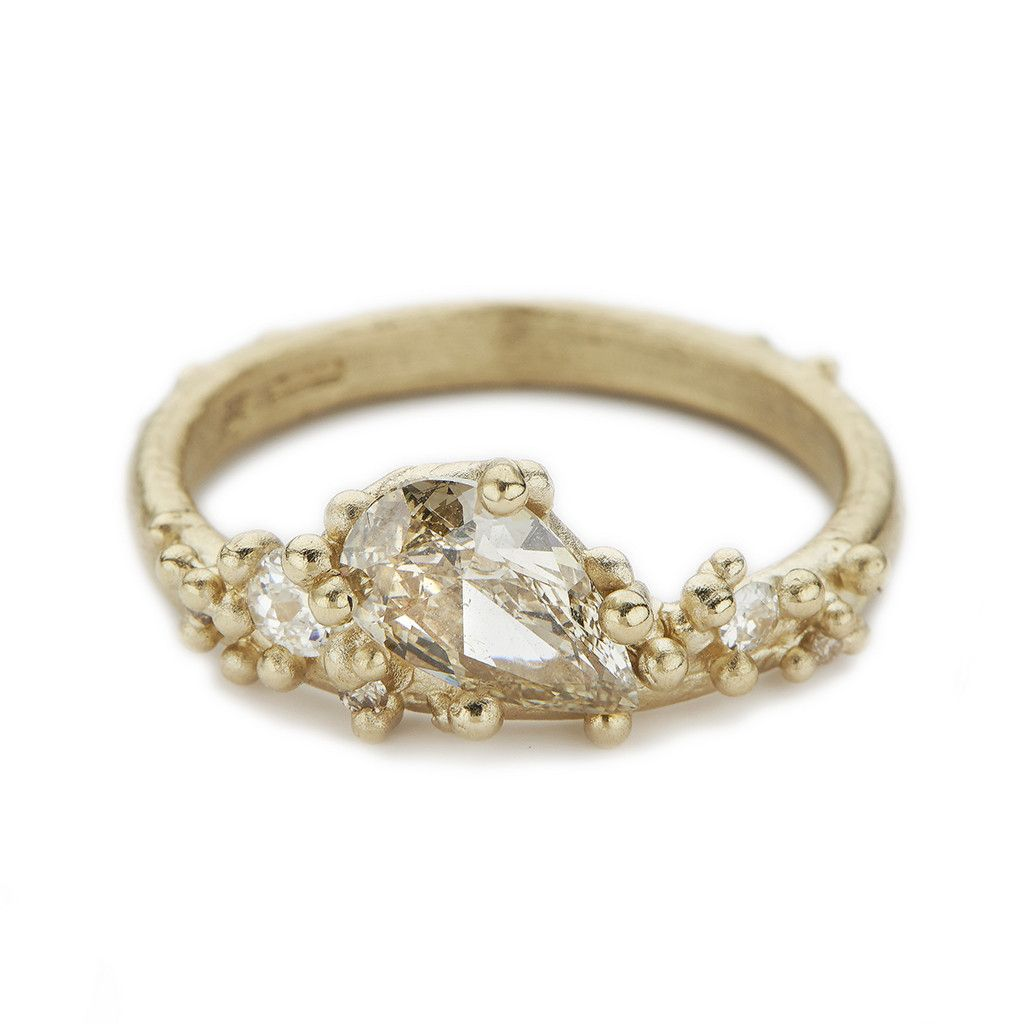 A unique alternative engagement ring from Ruth Tomlinson featuring an asymmetrical arrangement of champagne diamonds cast in yellow gold, handmade in London.